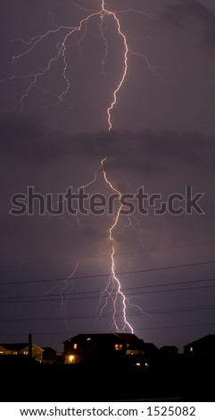 A long lightning bolt striking a residential area.
