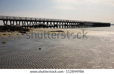 a long pier at the ocean during low tide
