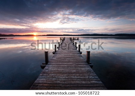 a long pier leading out onto the lake, sunrise on lake, long way out - stock photo