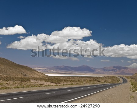 A long road across the desert. - stock photo