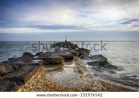 A long sea groyne with beacon on the beach at Hengistbury Head near Bournemouth in Dorset. - stock photo