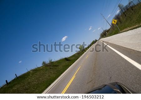 A long shot at a slanted angle of a road with traffic stripes. - stock photo