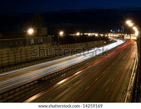 A long time exposure of a urban night traffic lights. Road perspective - stock photo