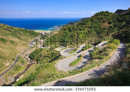 A long winding road going downhill with green mountains and the ocean visible. - stock photo