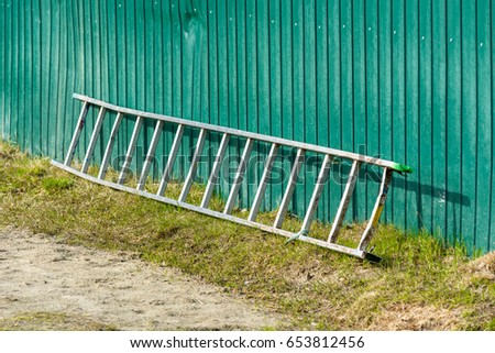A long wooden ladder lying at green fence.