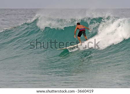A longboarder takes off on a clean wave in Phuket, Thailand - stock photo