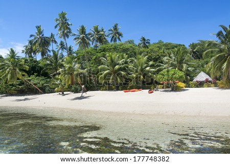 A look at a Fijian tropical resort from the water showing its lush surroundings and recreational kayaks on the beach along with a small, thatched cabana for changing and getting out of the sun. - stock photo