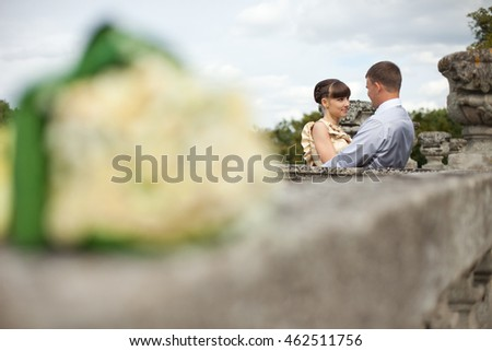 A look from behind the wedding bouquet on bride and groom standing on the balcony