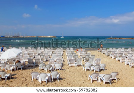 A lot not occupied beach chairs on perfect beach of the Mediterranean sea