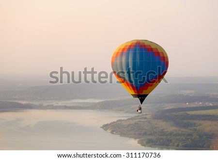 A lot of balloons start they flight over field and forest - stock photo