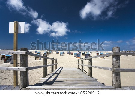a lot of beach chairs at the beach of Sankt Peter Ording,  North Sea, blue sky in summer - stock photo