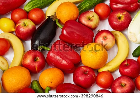 A lot of beautiful fruit and vegetables are spread out on a white background