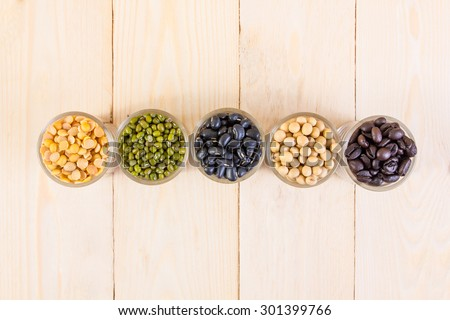 a lot of black bean, green beans, soybean, roasted coffee beans on wood texture background - stock photo