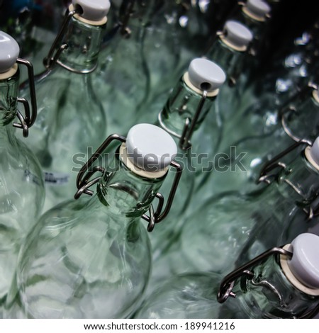a lot of bottles with caps lined up in a production plant - stock photo