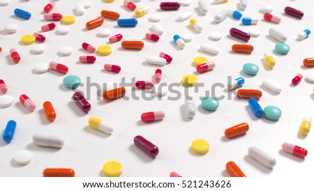 A lot of colored capsules and pills on white background