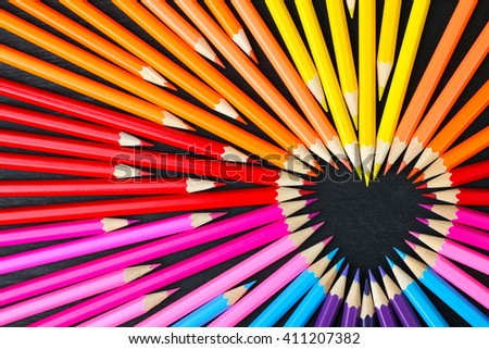 a lot of colored pencils closeup on wooden background laid out in the shape of a heart - stock photo