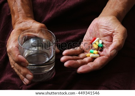 A lot of colored pills and a glass of water in old hands. Painful old age. Health care of older people - stock photo