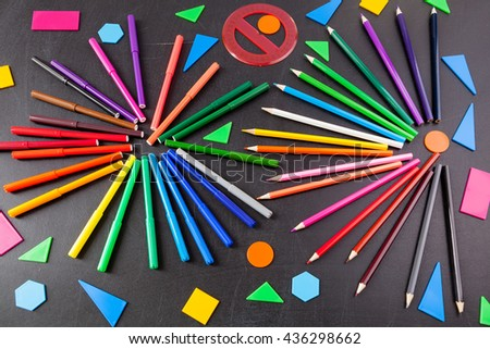 "A lot of colorful felt-tip pens and colorful pencils in circles and geometric figures on the black school chalkboard as background, concept ""Back to school"" - stock photo"