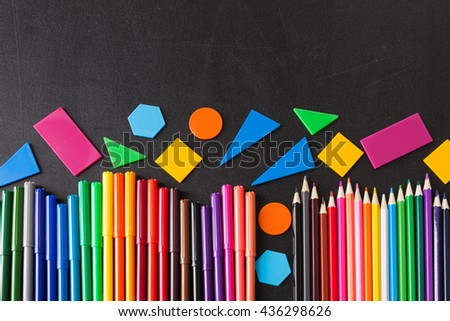"A lot of colorful felt-tip pens and colorful pencils in row and geometric figures on the black school chalkboard as background, concept ""Back to school"" - stock photo"