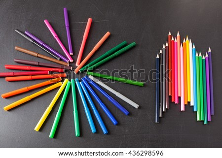 "A lot of colorful felt-tip pens in circle and colorful  pencils in row on the black school chalkboard as background, concept ""Back to school"" - stock photo"