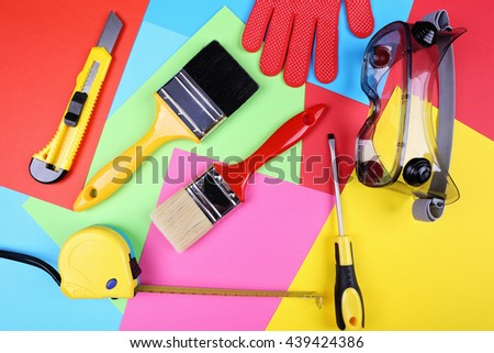 A lot of construction tools for the repair of housing. Two brushes to paint, stationery knife, measuring tape, screwdriver, safety goggles and gloves on colored paper.