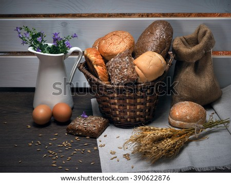 A lot of different bread, ears of wheat, eggs and pitcher with flowers - wild bells