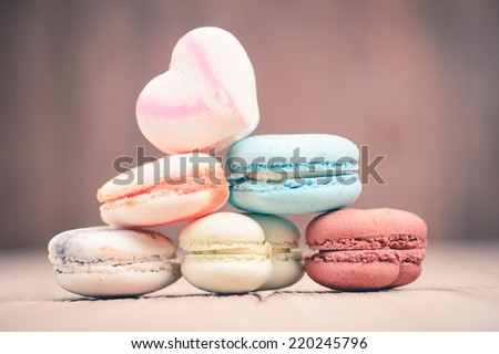 A lot of french colorful macarons on a woody floor in vintage tone style - stock photo