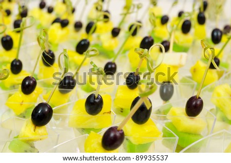 a lot of fruit canapes on buffet table, catering, shallow DOF - stock photo