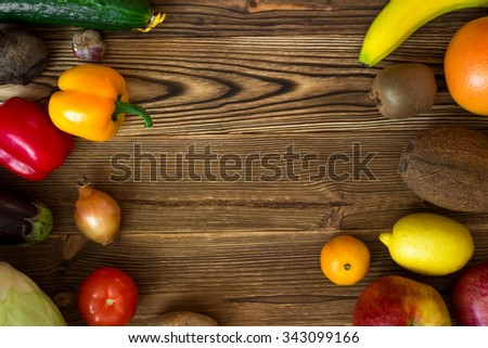 a lot of fruits and vegetables, cabbage, onions, eggplant, cucumber, tomato, pepper, banana, apple, orange, lemon, kiwi, in the form of frames on a wooden background