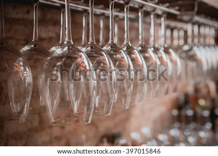 A lot of glasses hanging in a row, Selective focus - stock photo