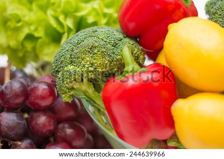 A lot of healthy colorful different vegetables and fruits - broccoli, paprika, lemon, salad and purple grapes