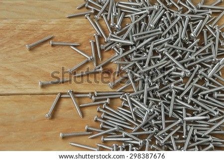 A lot of metal sharp screws are placed on a wooden background.