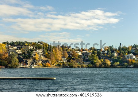 A lot of residential houses with big windows on Lake Shore. Sweden suburb with many houses on rocks stones near water. Beautiful autumn background with blue sky,trees and lake. Place for your own text - stock photo