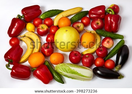 A lot of ripe vegetables and fruit are spread out on a white background - stock photo