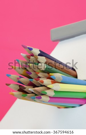 A Lot Of Sharped Colored Pencils Are Sticking Out From The Heart Shaped Window In The Home White Wall Isolated On Pink Background, Vertical Image - stock photo