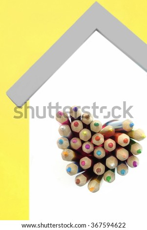 A Lot Of Sharped Colored Pencils Are Sticking Out From The Heart Shaped Window In The Home White Wall Isolated On Yellow Background, Vertical Image - stock photo