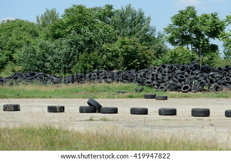a lot of used tires next to a drift track - stock photo