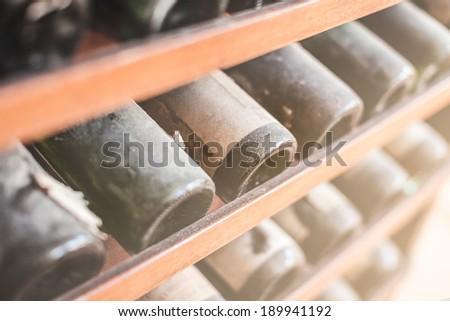 a lot of very old dusty wine bottles in an italian cellar - stock photo