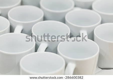 A lot of white tea cups. Selective focus. - stock photo