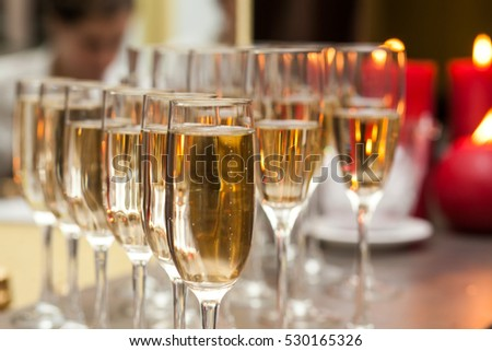 A lot of wine glasses with a cool delicious champagne or white wine at the bar.