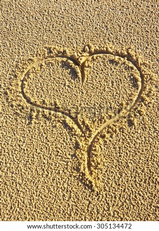 A love heart drawn in the sand to celebrate valentines day.  Romance/romantic concept. - stock photo