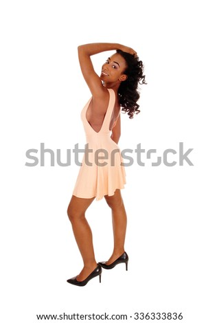 A lovely African American woman in a beige dress with long curly black hair, looking over her shoulder, isolated for white background.  - stock photo
