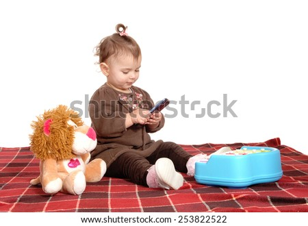 A lovely baby girl sitting on a blanket on the floor holding a cell phone, 