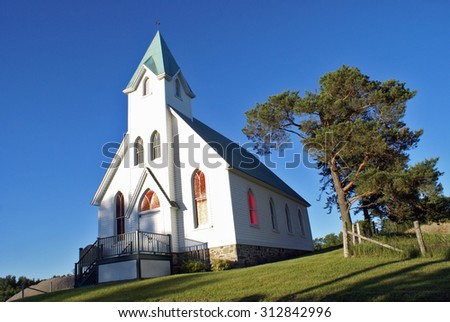 A lovely composition of a white church in the charming countryside. - stock photo