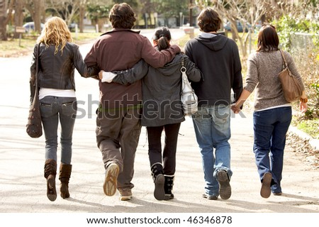 A lovely  family holding eachother walking away from camera - stock photo