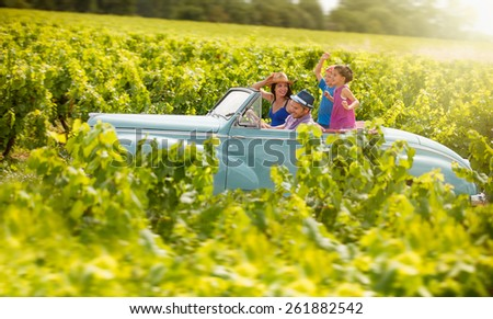 A lovely family is going on vacation in a convertible retro car, they drive on a country road on a sunny day - stock photo