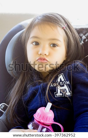 A lovely girl making funny face and sitting in a car seat - stock photo