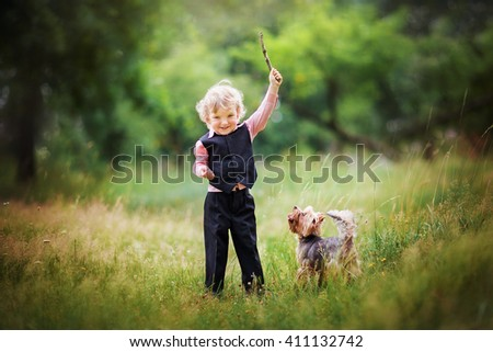 A lovely kid throwing a stick to his running pet. Cute little blonde boy playing with his dog.Happy summer day outdoors.Colorful photo. Friendship.