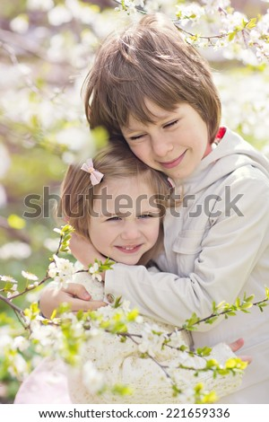 A lovely little girl and a cute boy embracing under a blooming cherry tree on a sunny spring day. Kids and flowers closeup - stock photo