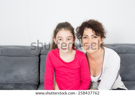 A Lovely little girl with her mother looking at the camera - stock photo